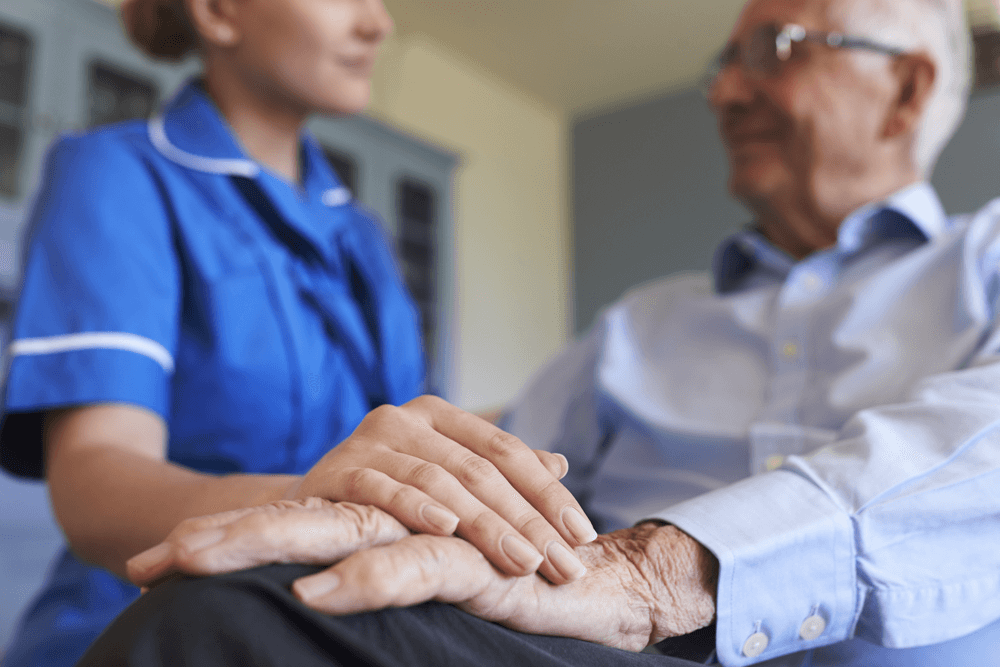Image of an elderly patient being comforted by a care worker