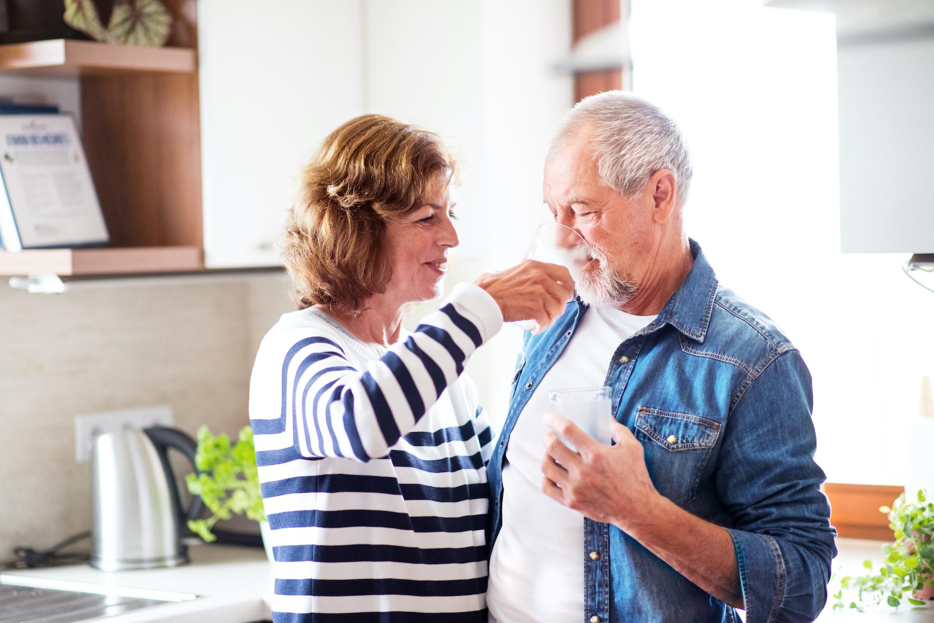 Eine Frau hilft einem älteren Mann seine Jacke anzuziehen