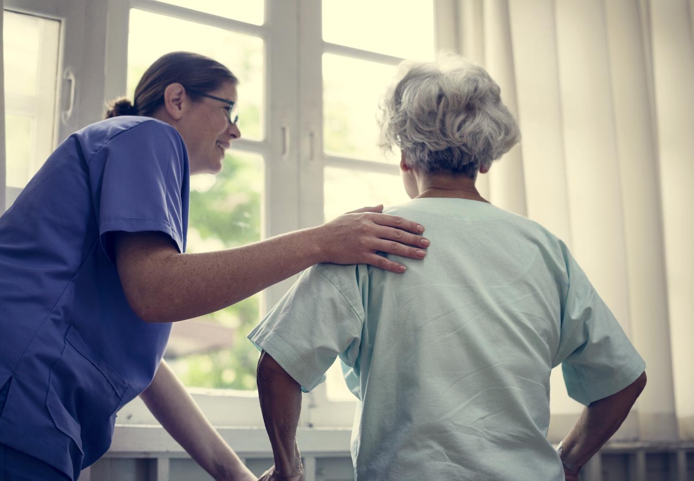 Eine Krankenschwester hält die Schulter einer älteren Dame fest