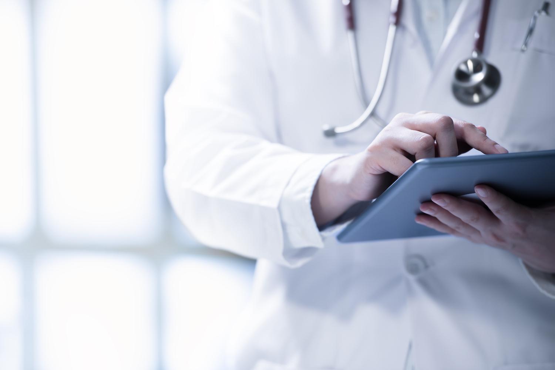 Ein Arzt schaut etwas auf einem Tablet nach
