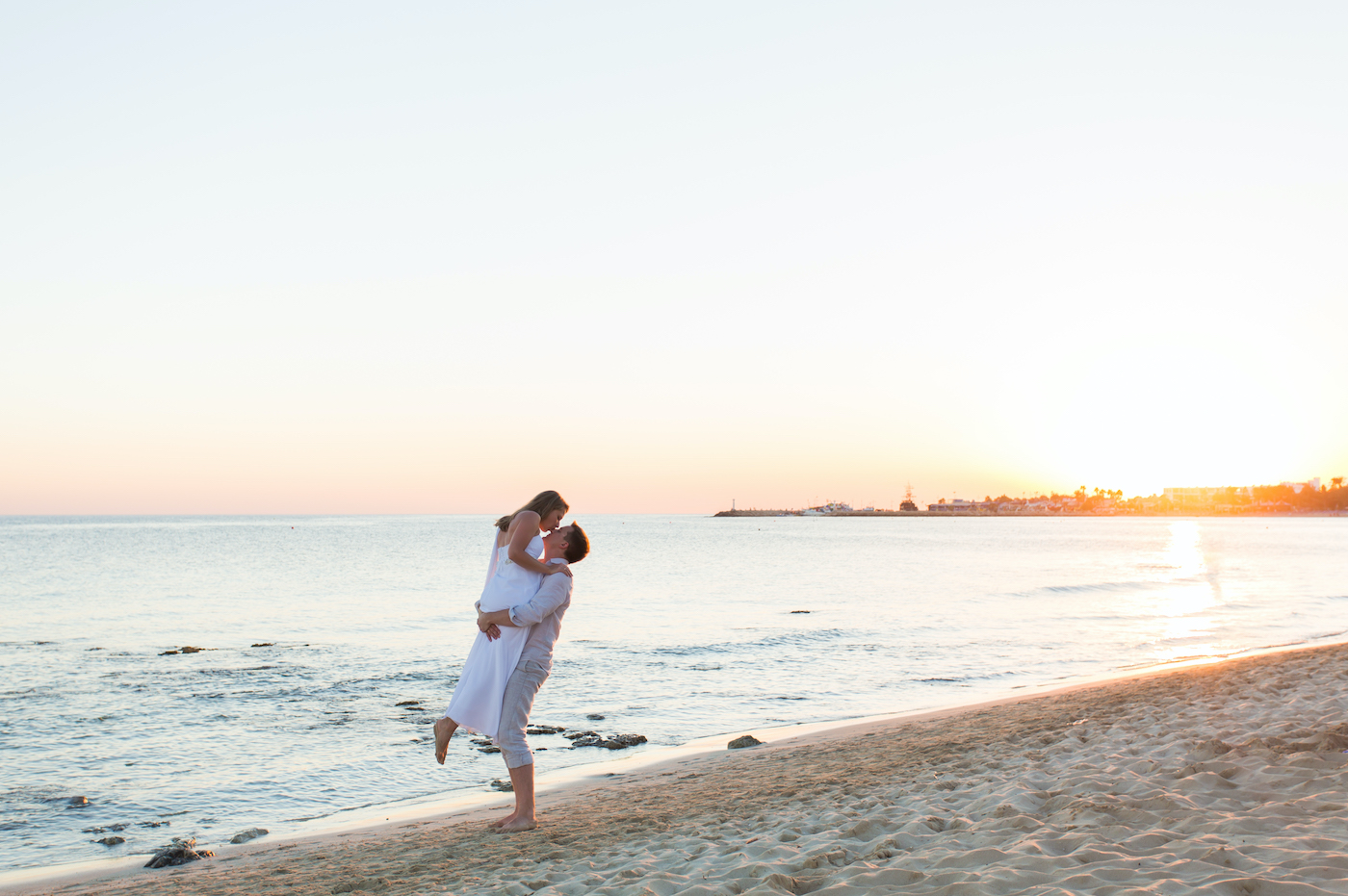 Ein Mann hebt eine Frau hoch an einem Strand mit Meer im Hintergrund