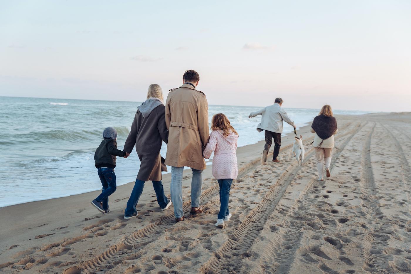 Eine Vierköpfige Familie läuft an einem Strand entlang und vor Ihnen ein Pärchen mit einem Hund