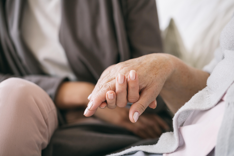 Jemand hält fürsorglich die Hand eines anderen