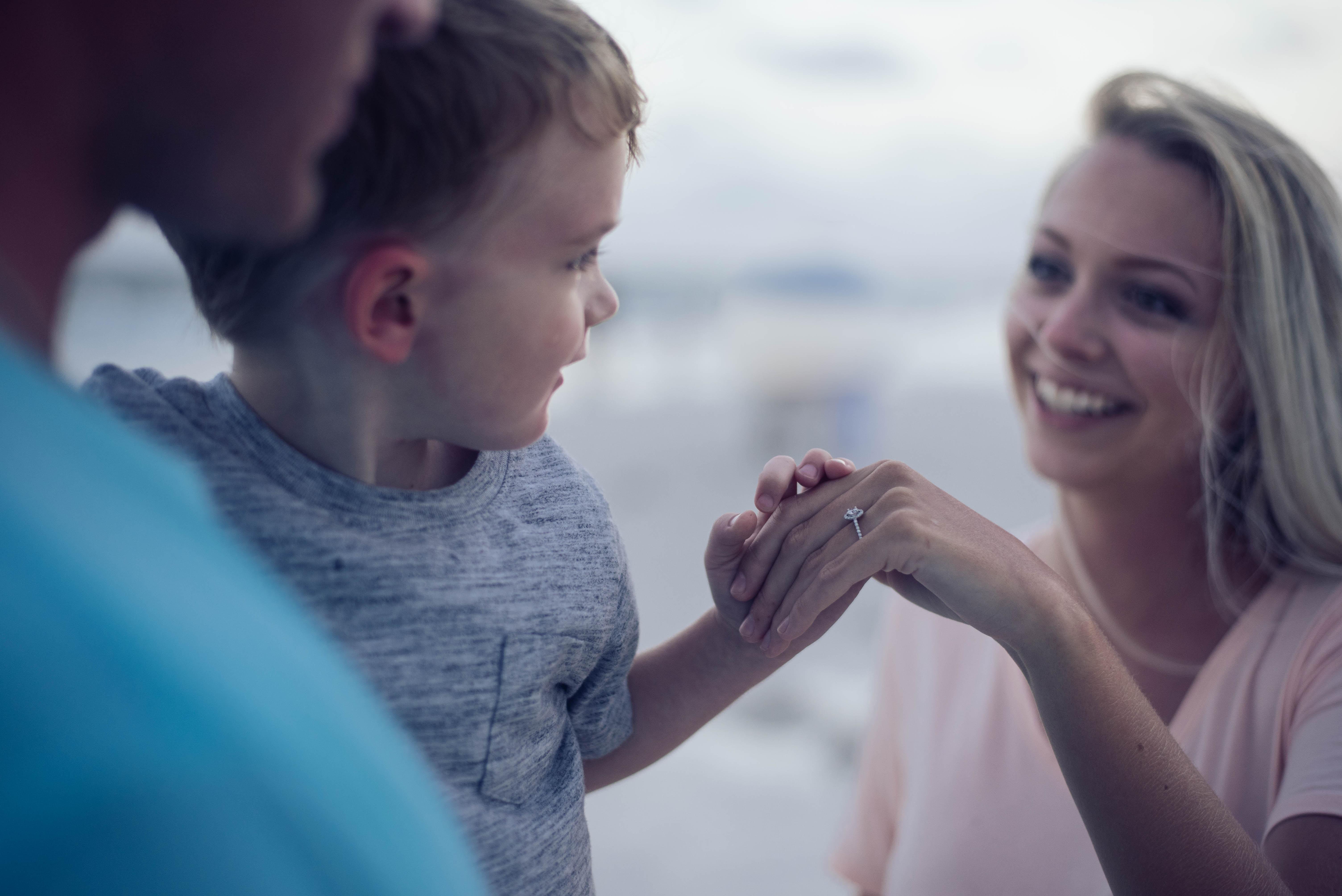 ein Kleinkind dreht sich zu einer lachenden Frau um und gibt ihr seine Hand