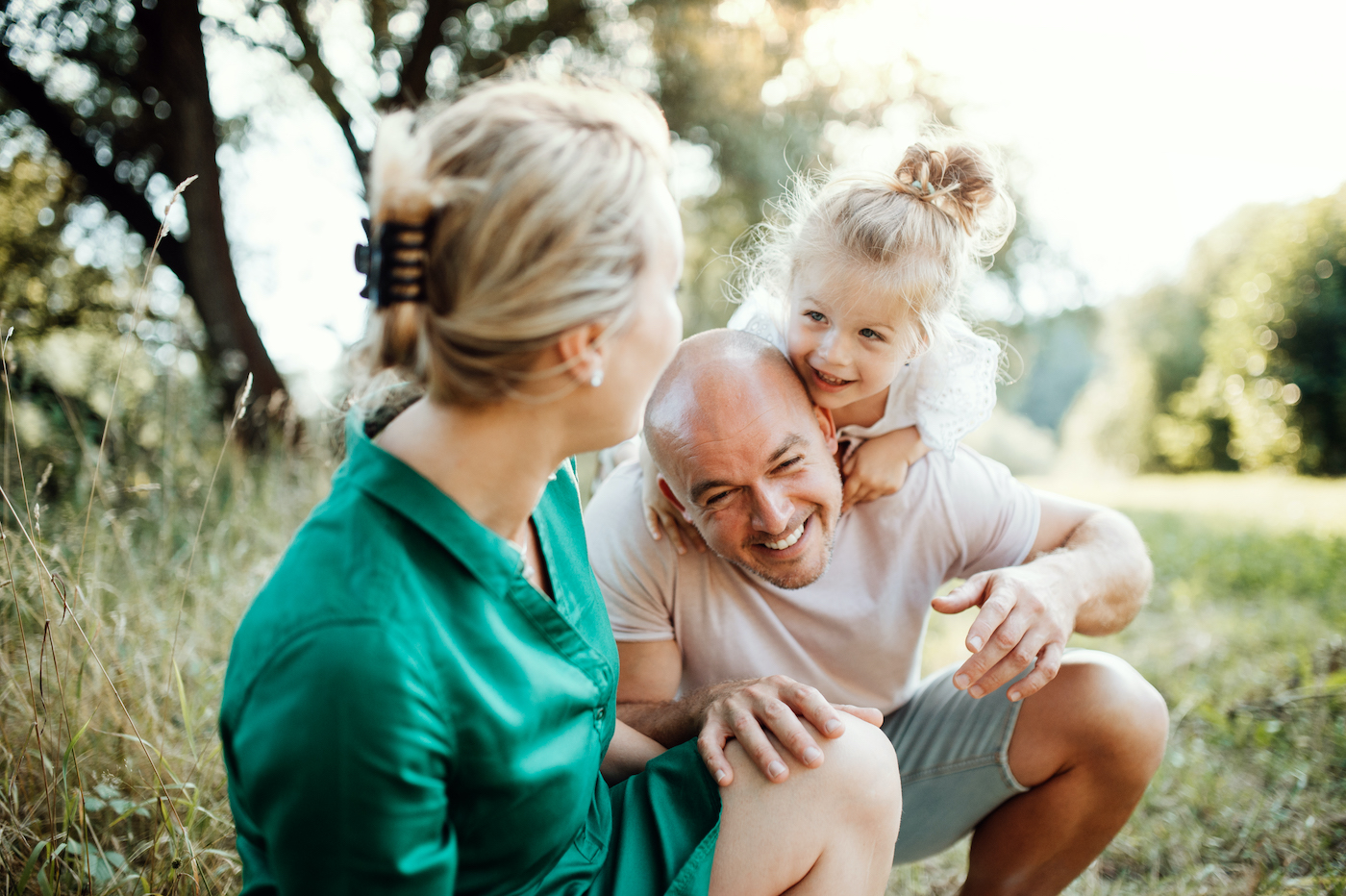 Eine Frau dreht sich zu einem lachenden Mann um, auf dessen Rücken ein kleines Mädchen rumspielt