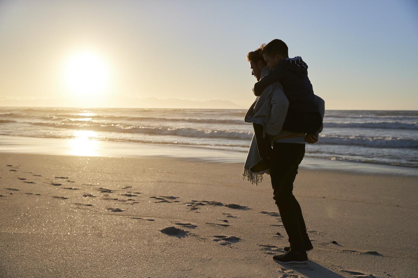 Ein vollgepackter Mensch mit Rucksack läuft am Strand entlang
