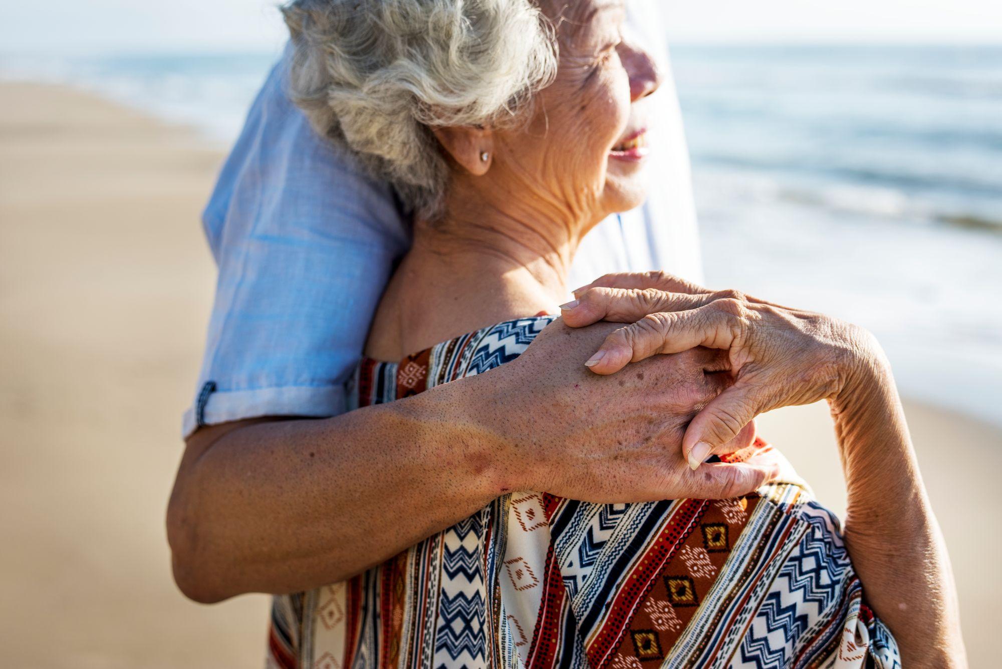 Eine alte Frau schaut lachend auf das Meer mit ihrem Partner.