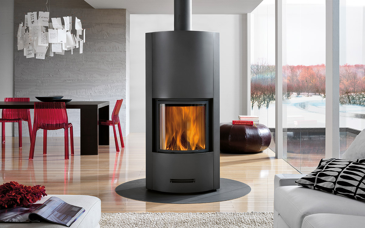 Calore freestanding wood burner with fan assist, polished solid wood floor, raw cement feature wall.
