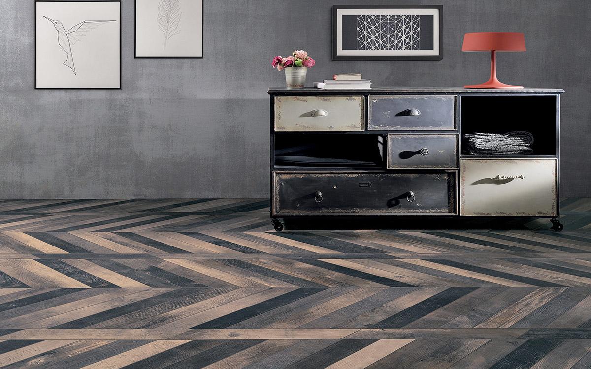 Chevron wood floor design, cement look wallpaper, antique chest of draws.