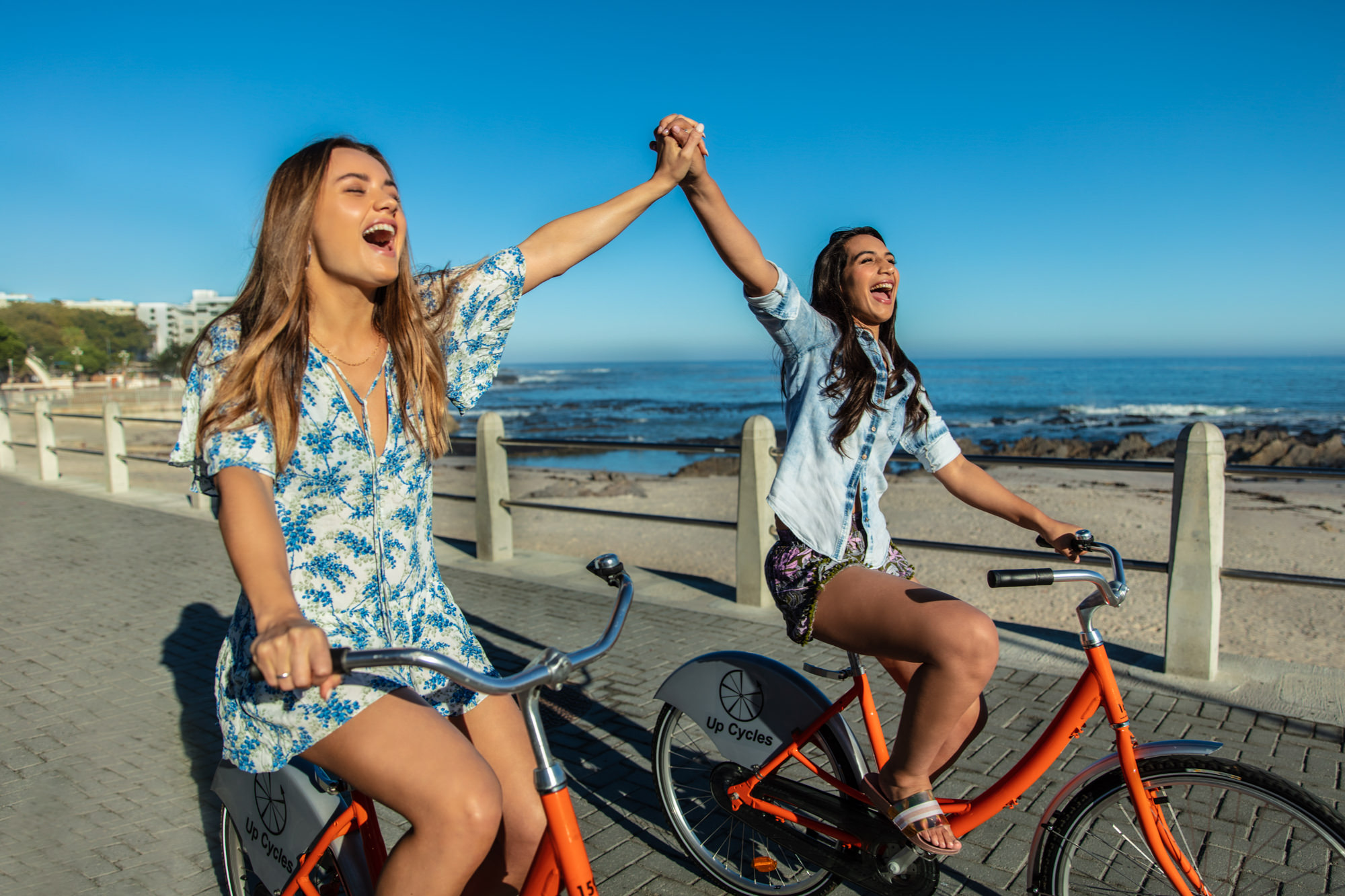 Image of girl friends riding bicycles on the Promenade in Sea Point, Cape Town for Tsogo Sun's Image Library & Content Library by Michelle Wastie Photography