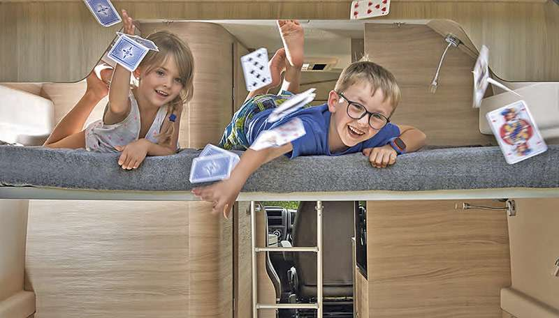 Bild von zwei Kindern in einem Wohnmobil die lachend Spielkarten in die Luft werfen.