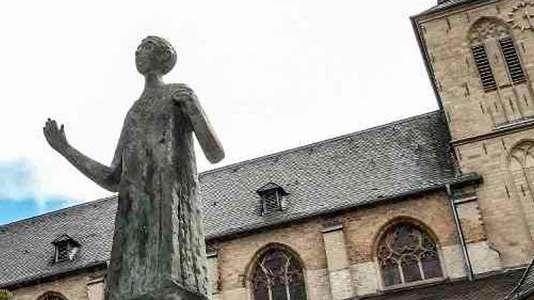 Ein Bild einer Statue und einer Kirche in der Stadt Mönchengladbach.
