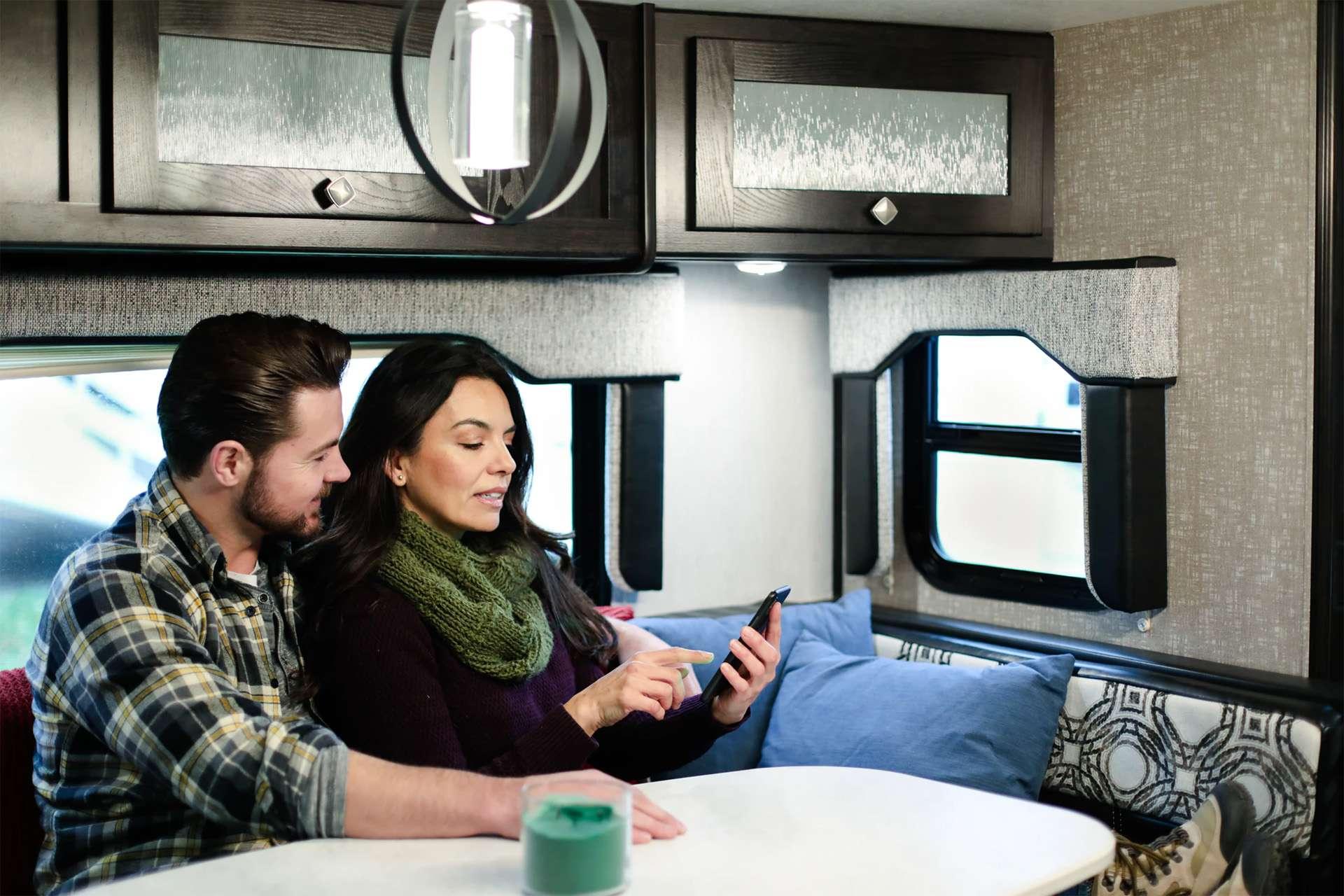 Bild eines Pärchens in einem Wohnmobil, welches auf ein Smartphone schaut.