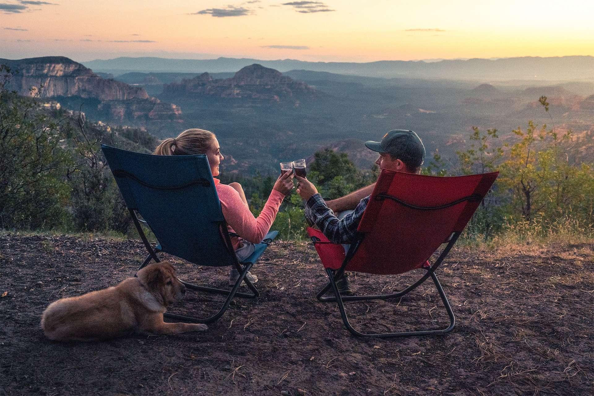Bild eines Pärchens beim Camping mit einem Hund.