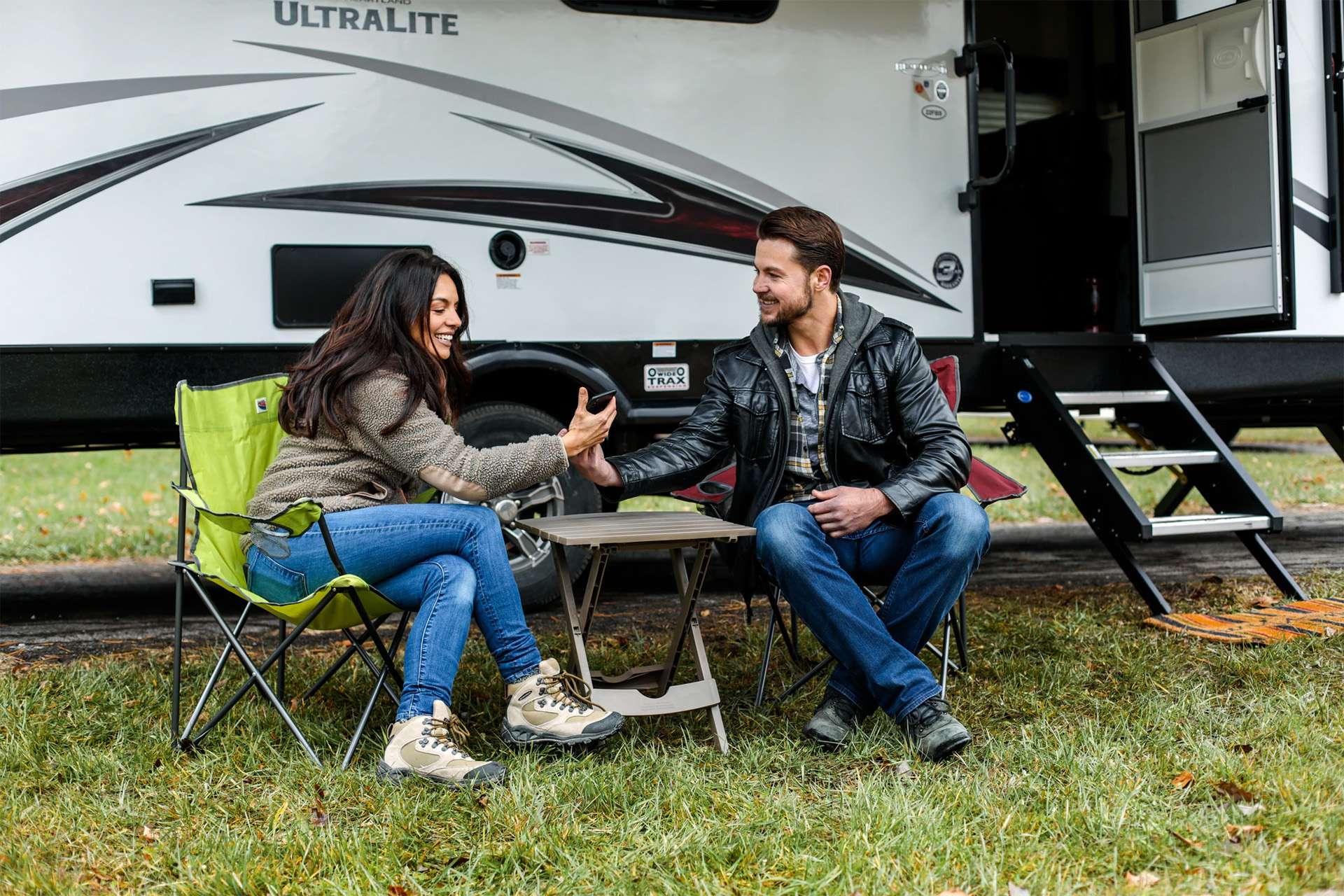 Ein Bild von zwei Personen vor einem Wohnwagen mit einem Handy.