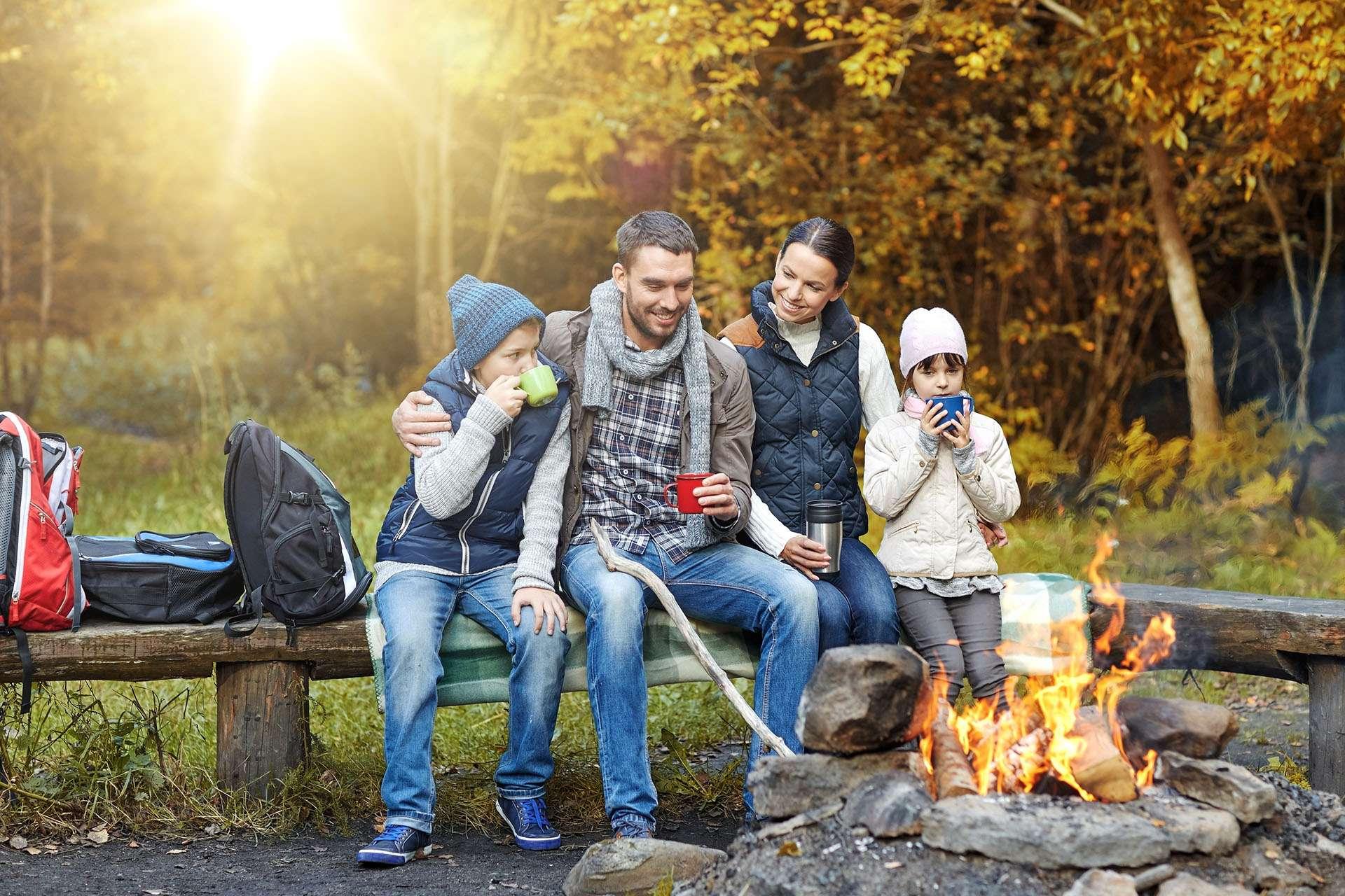 Bild einer Familie beim Camping an einem Lagerfeuer.