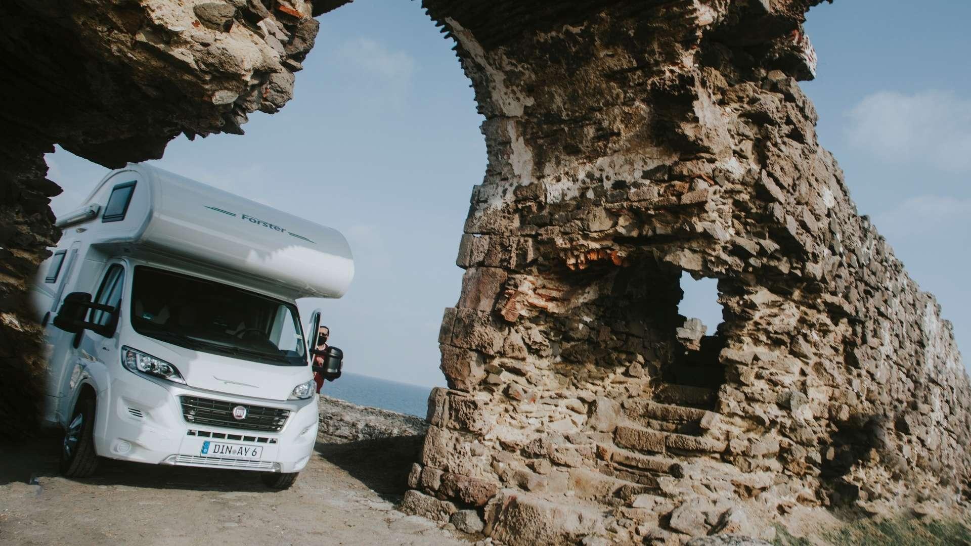 Wohnmobil auf Reise unter einem Bogen aus Stein.