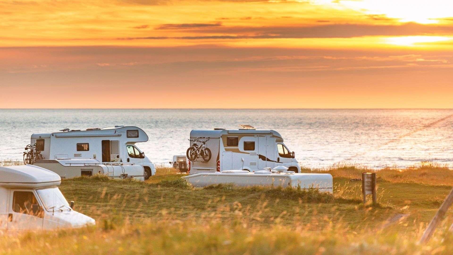 Wohnmobile am Meer mit Sonnenuntergang.