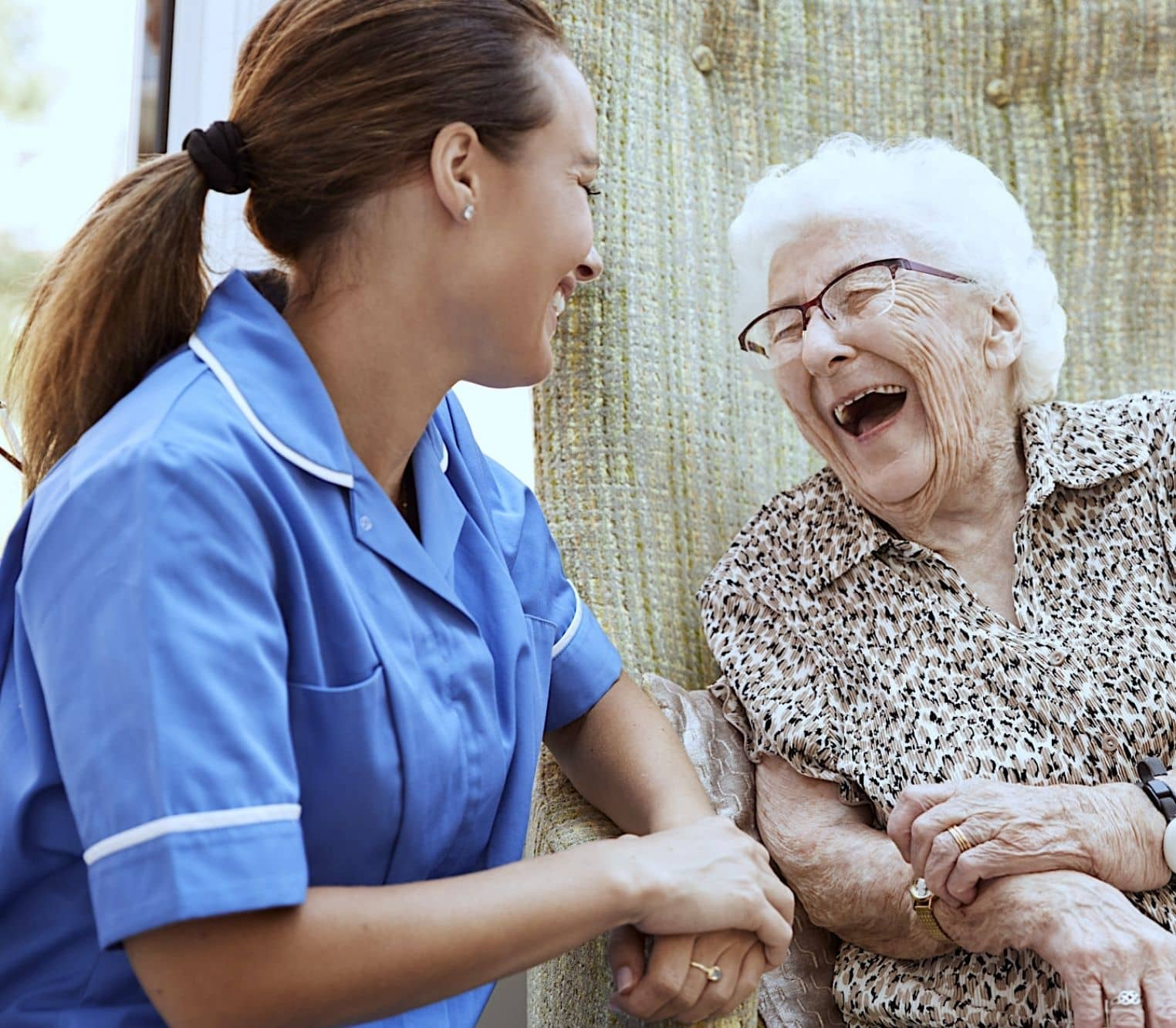nurse with elderly patient laughing