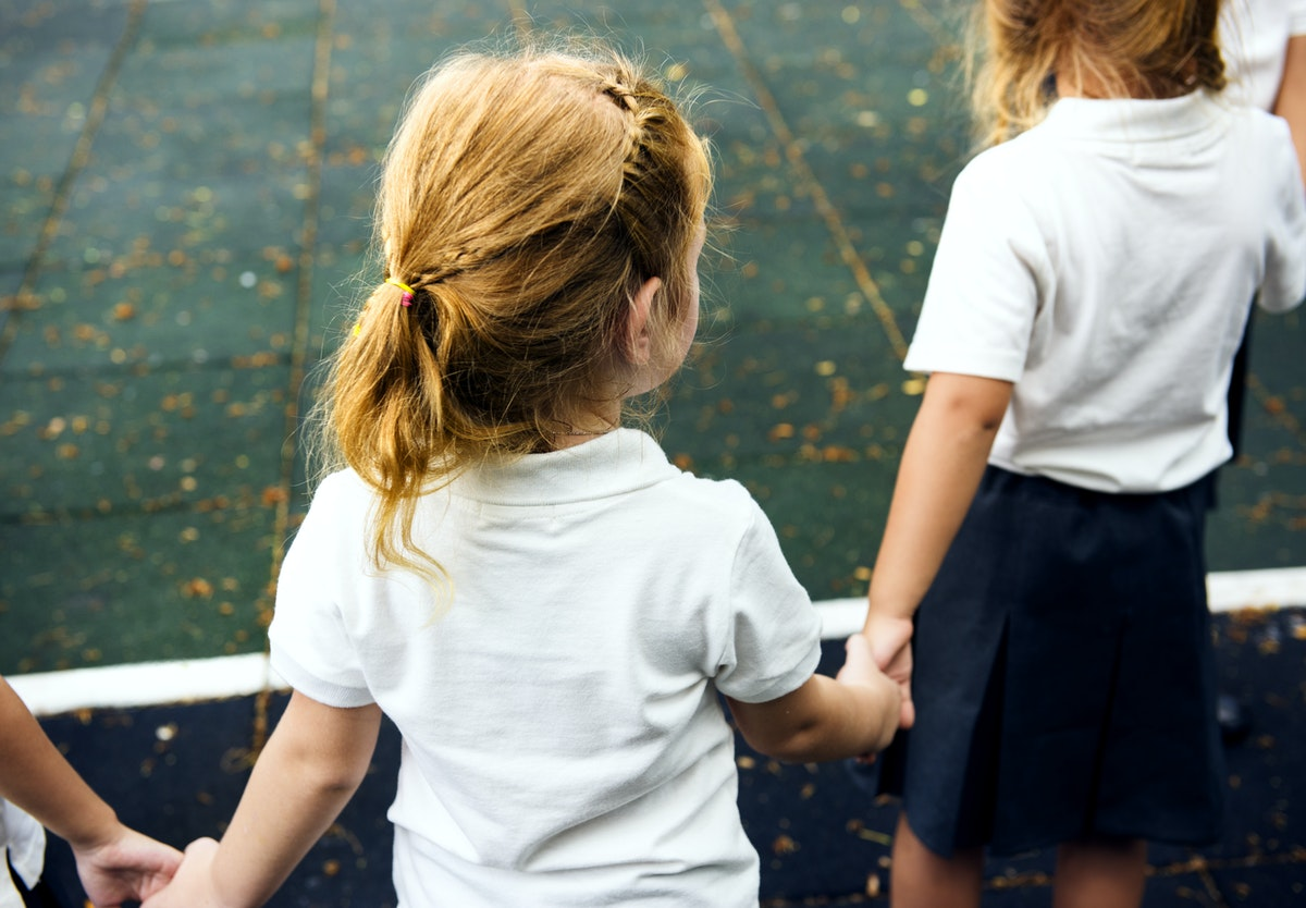 Small child with pony tail in circle holding hands with two other children in circle