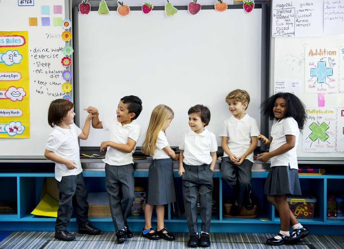 Multi Racial children laughing and talking in bright classroom
