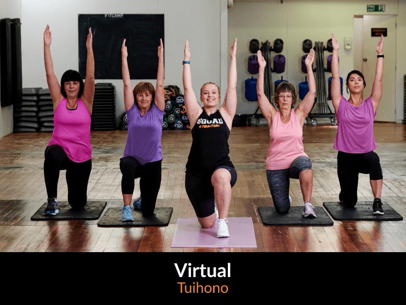 Five women kneeling at the gym with their arms raised