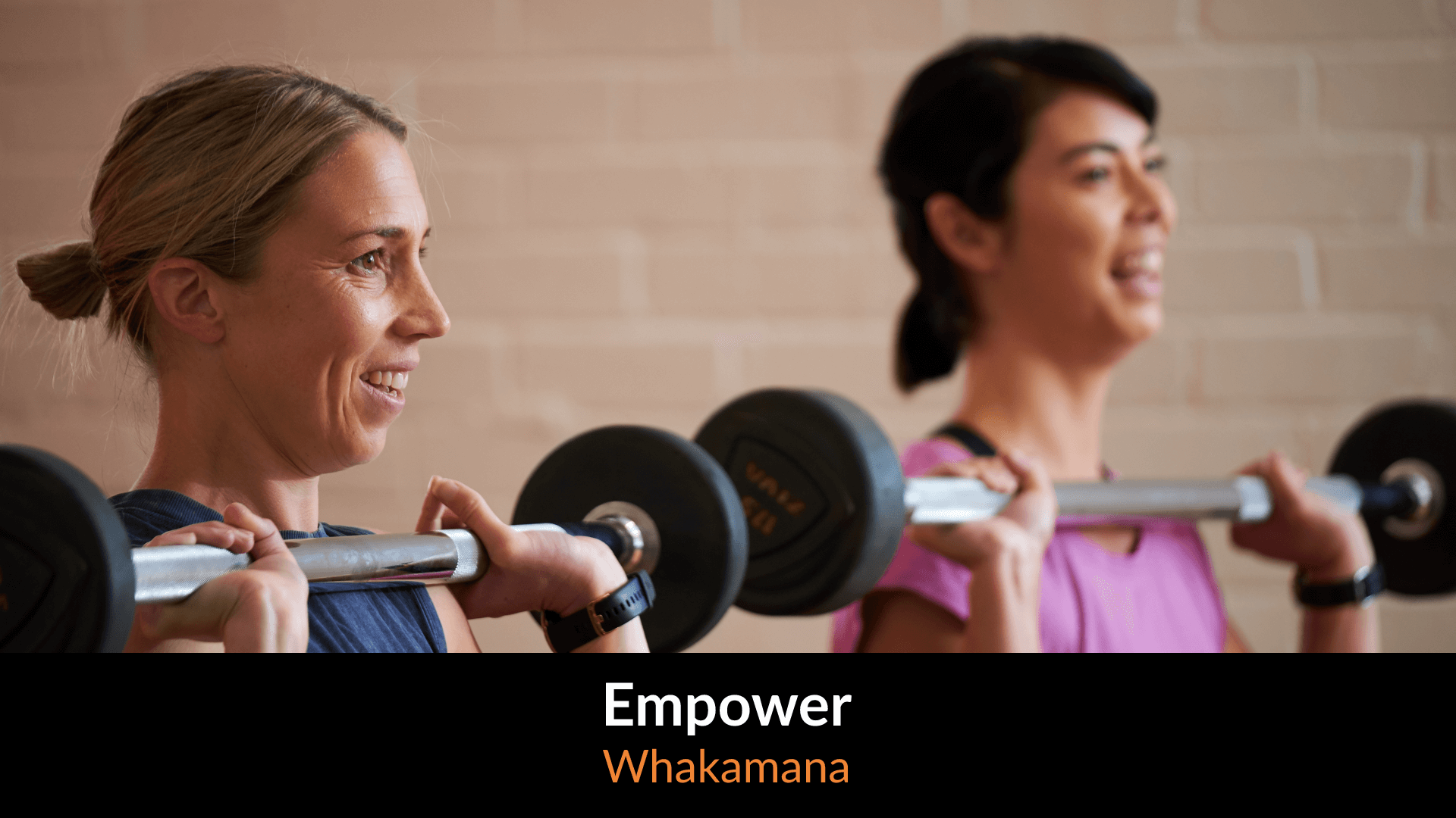 Two women smiling lifting weights