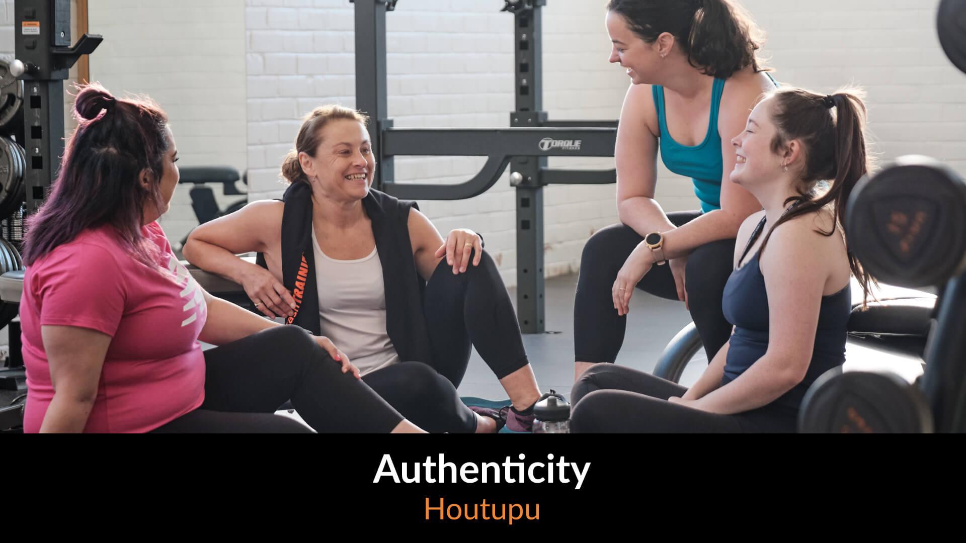 Four female gym members sitting on a gym mat talking