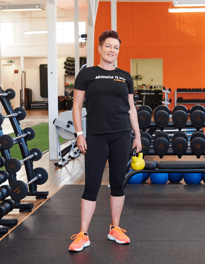A women standing with gym equipment behind her
