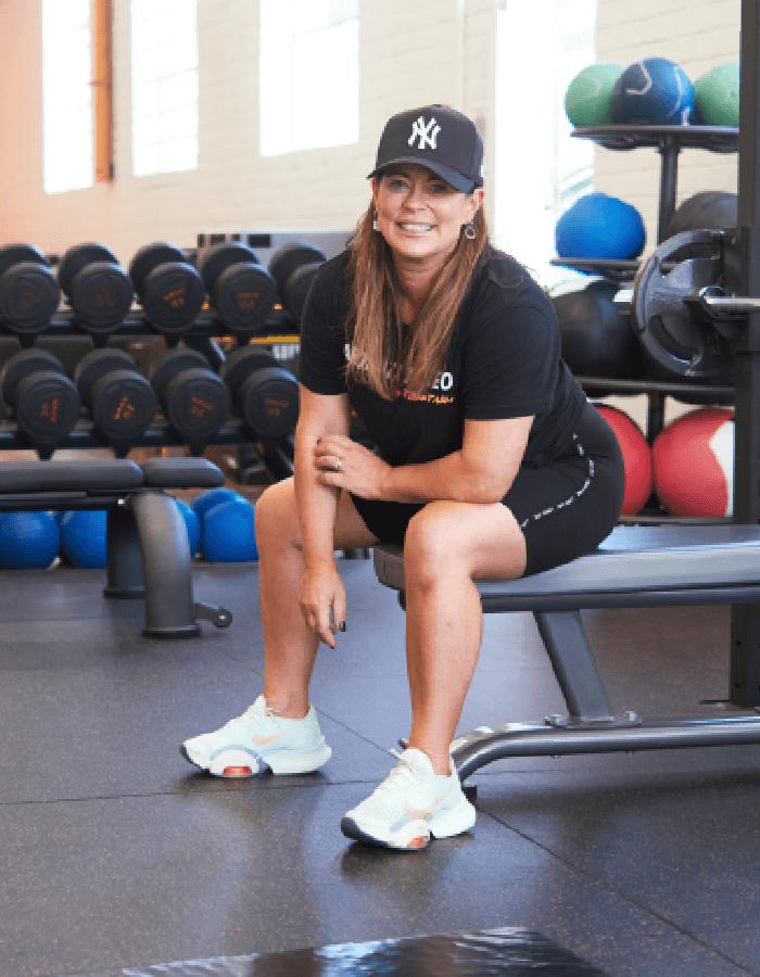 A women sitting on a gym bench