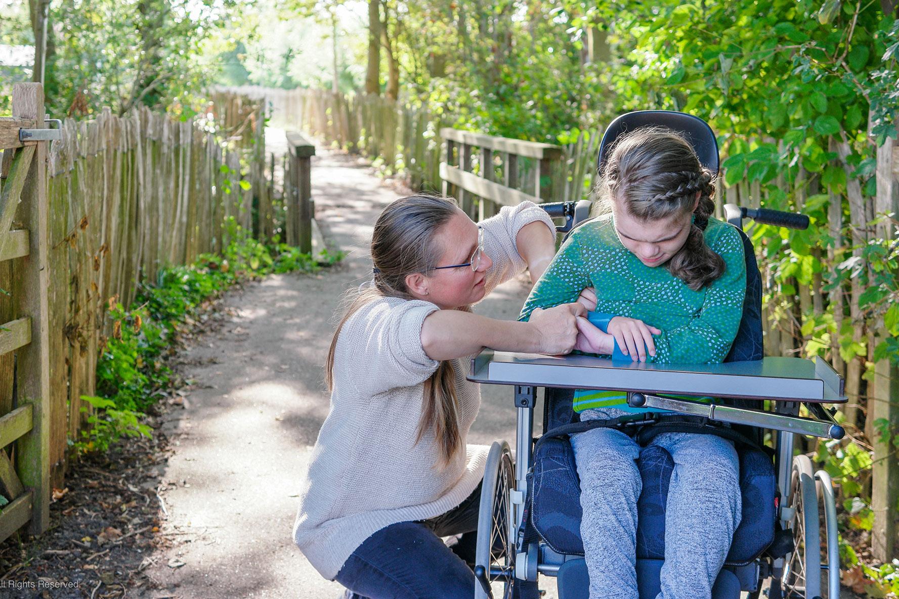 Begleiterin kuemmert sich um Maedchen im Rollstuhl