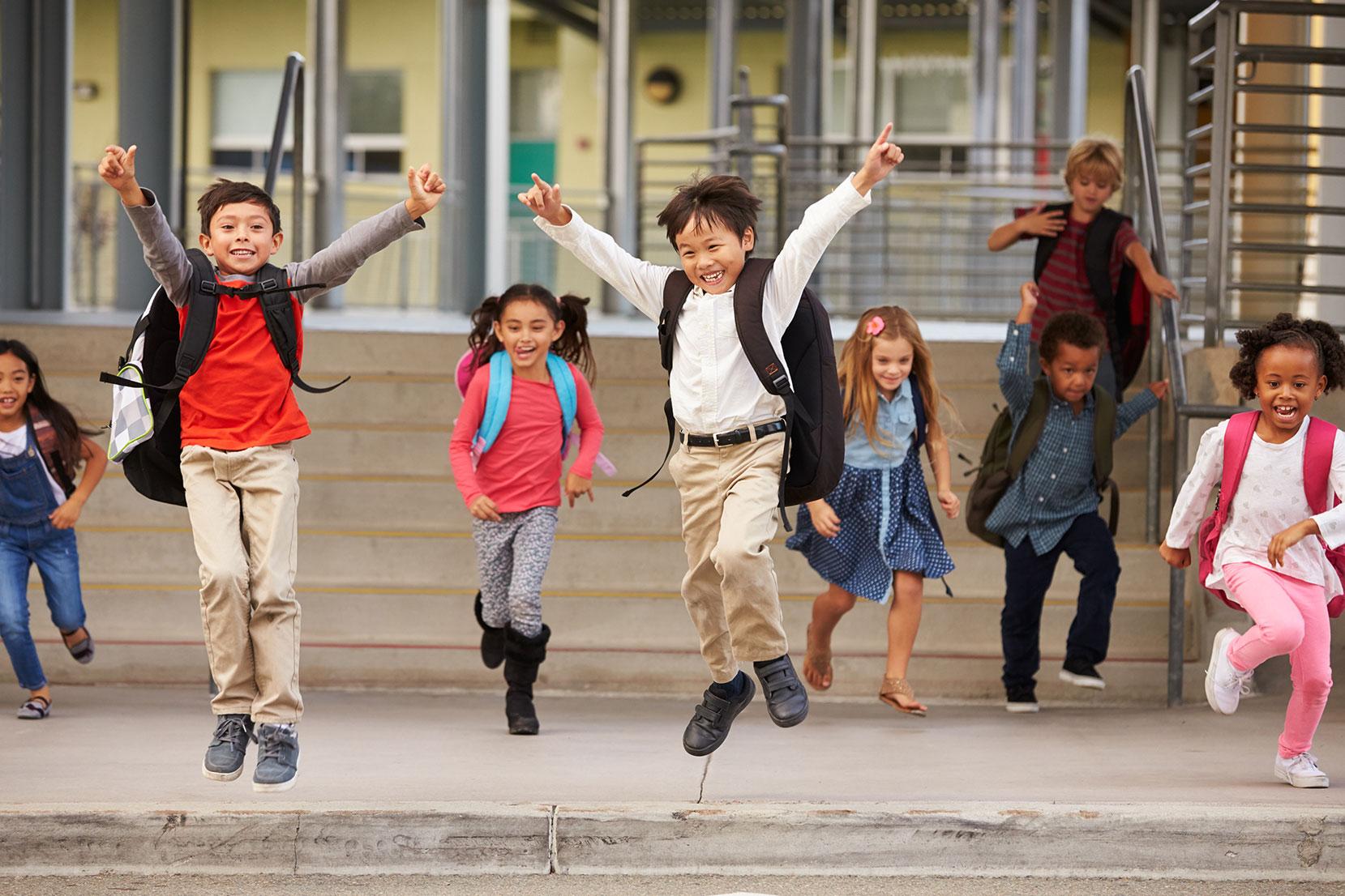 Kinder die erfreut aus der Schule rennen