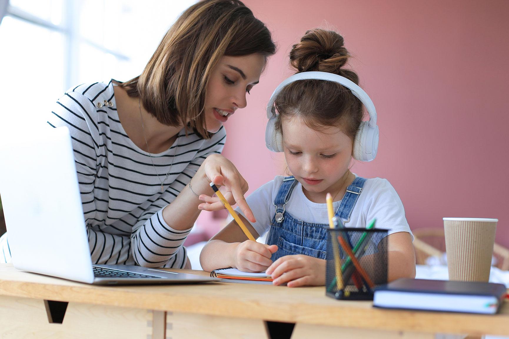 Begleiterin hilft Kind bei den Hausaufgaben