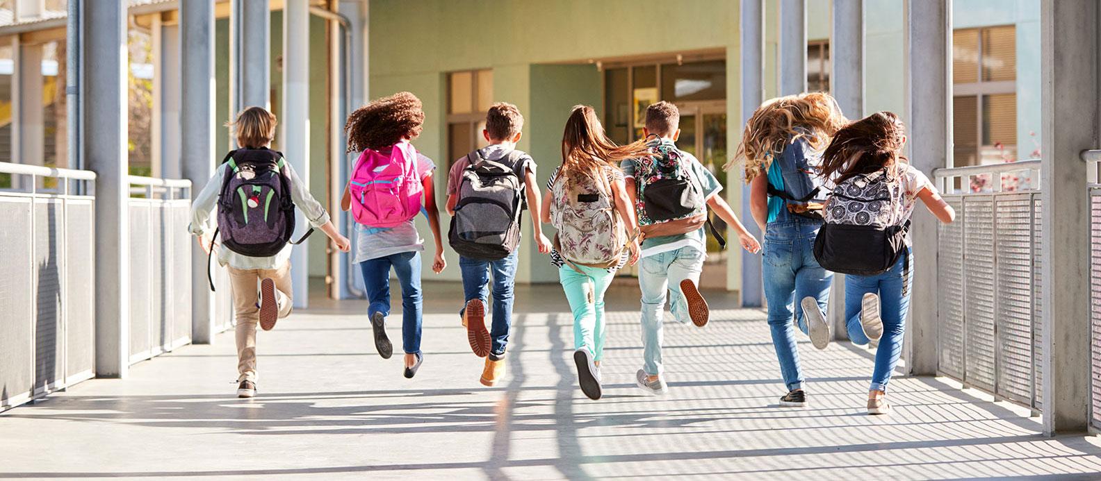 Kinder die erfreut in die Schule laufen