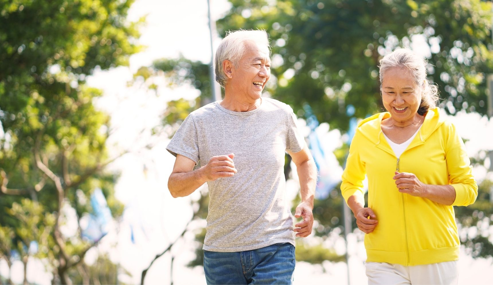 Senior Asian man and woman smiling and going for a jog together