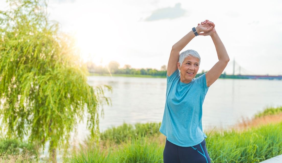 Senior woman stretching her arms while on a walk