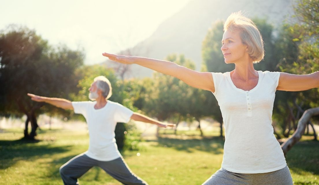 Senior man and woman doing yoga in a park