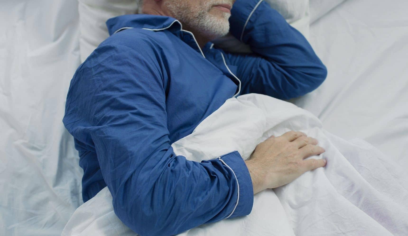 Elderly man sleeping in blue pajamas in bed