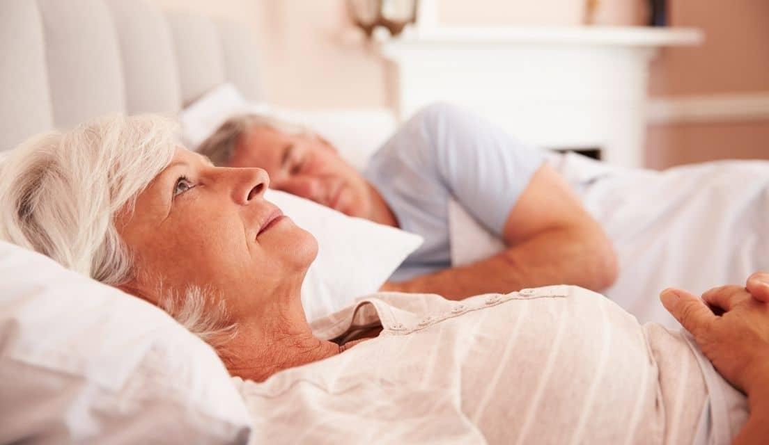 Senior woman lies awake in bed next to her sleeping husband