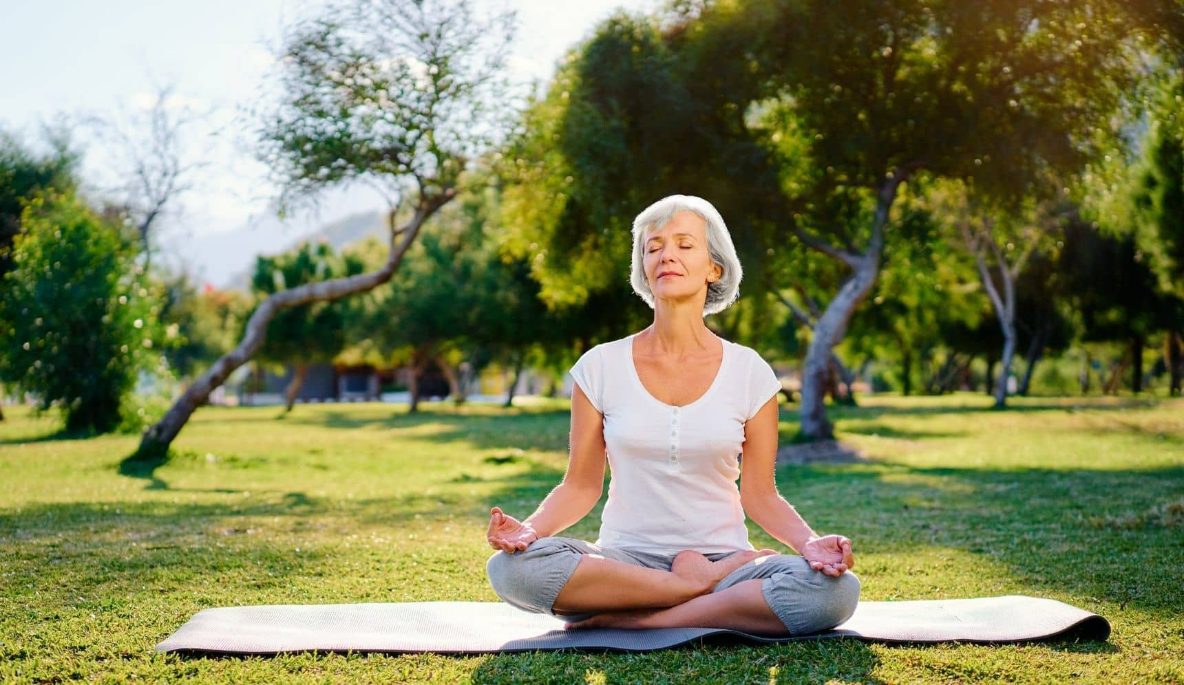 Senior woman meditating on a sunny day in a park