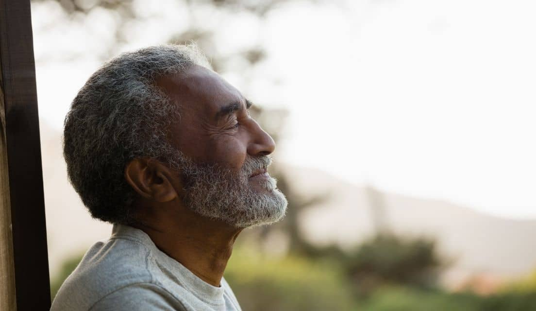 Senior man smiling while looking out