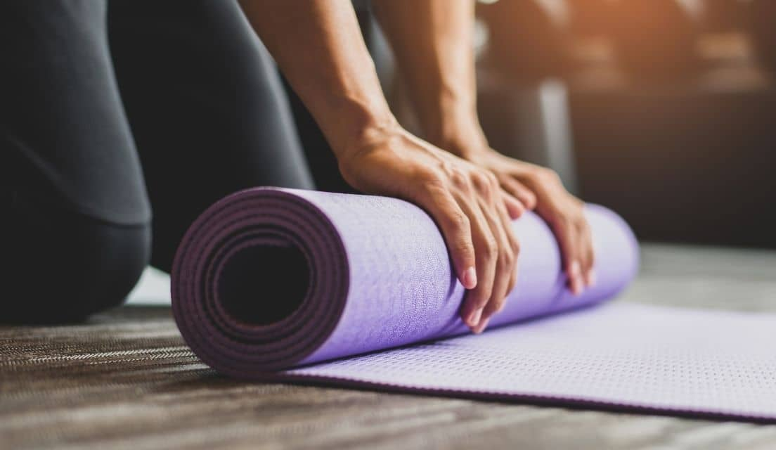 Hands of a woman are shown rolling up a purple yoga mat on the floor