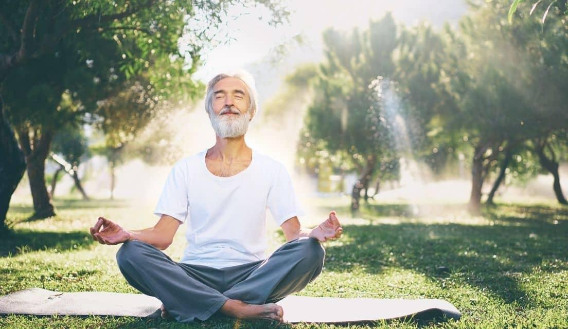 Senior man meditating in park and smiling