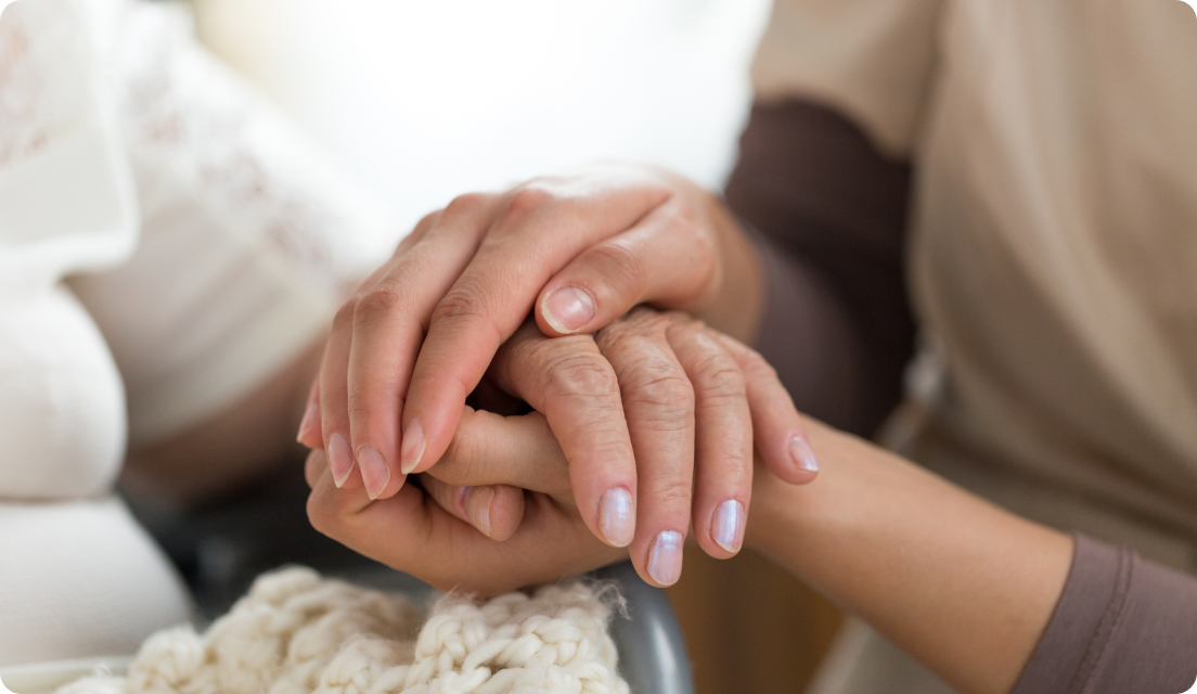 Close up of caregiver hands holding hand of elderly person