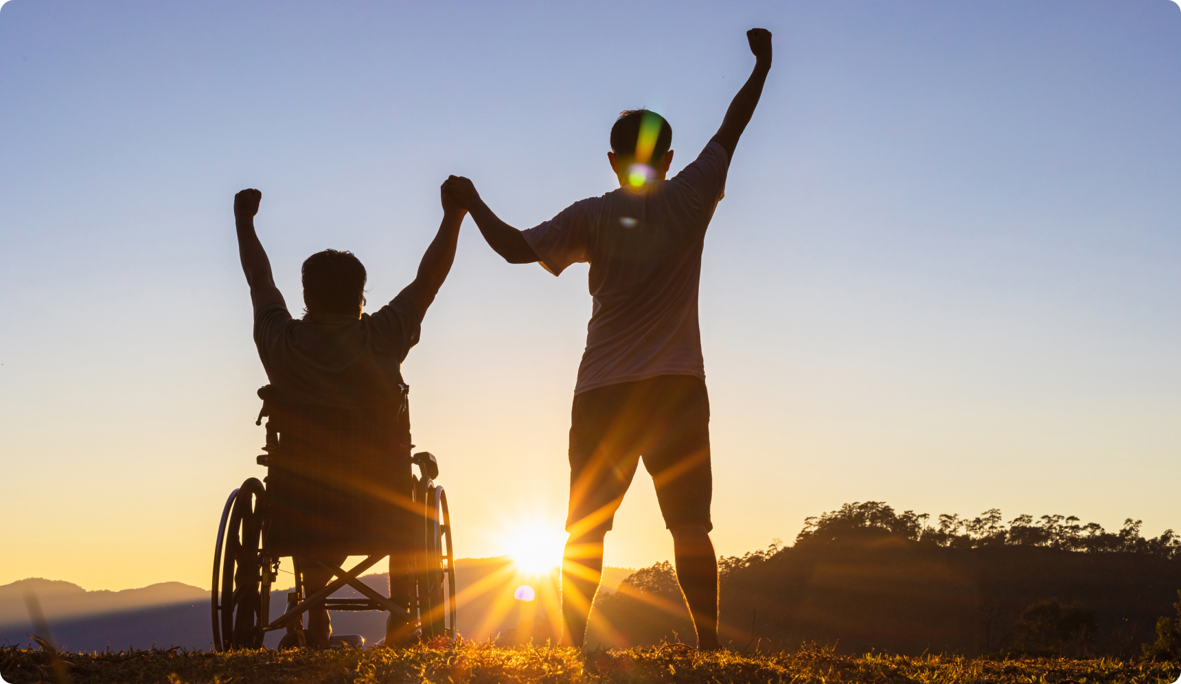 Silhouettes of person in wheelchair and person standing beside, with arms raised happily in the air