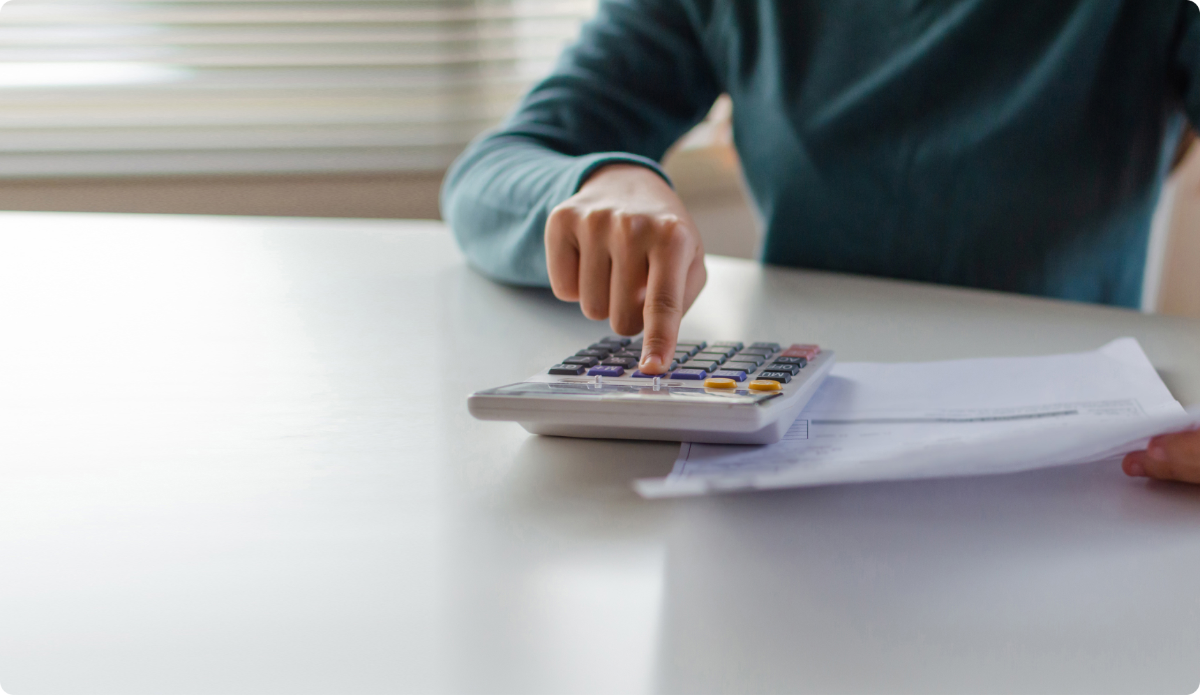 Person at table calculating costs on calculator