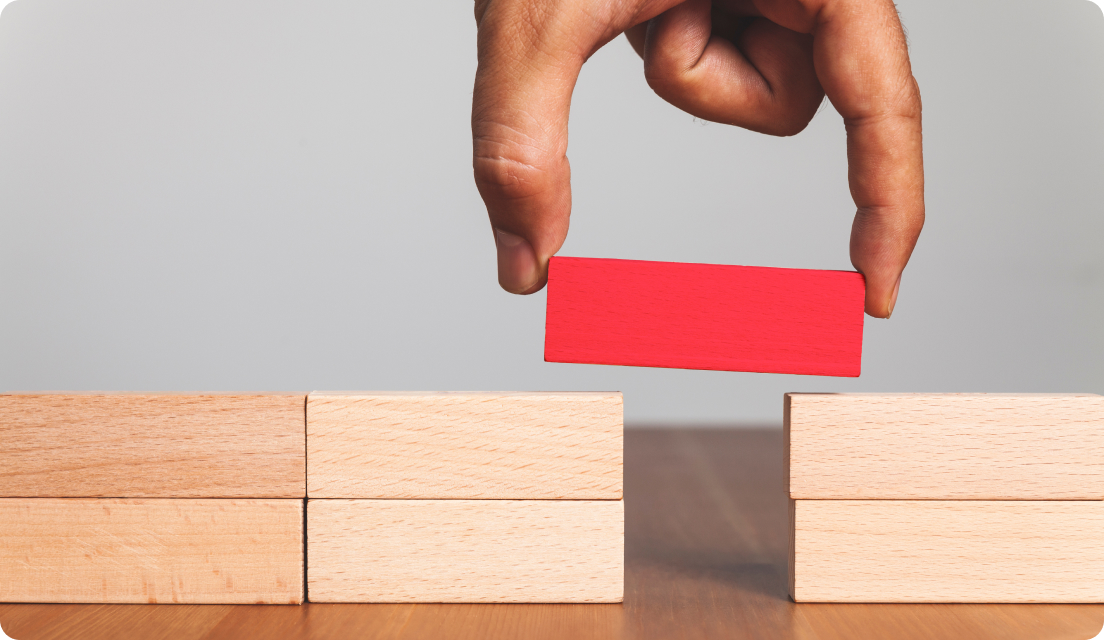 Man's hand placing a red wooden block on top of other wooden blocks to bridge the gap