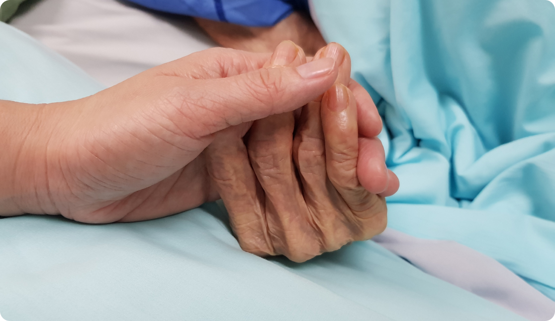 Caregiver holding hand of elderly patient