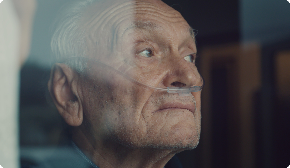 Senior man looking out window of hospital