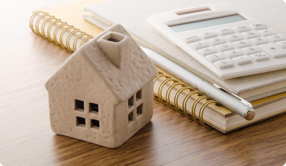 Figurine house on desk near documents and calculator